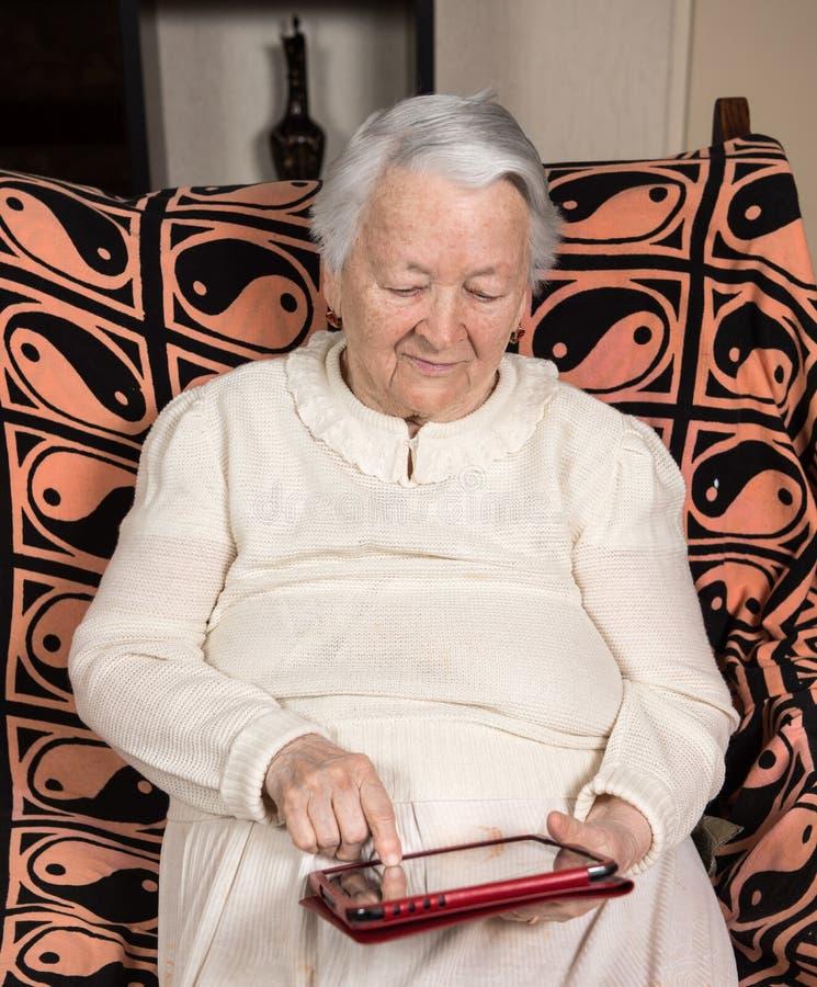 Portret dotyka cyfrową pastylkę stara kobieta zdjęcia stock