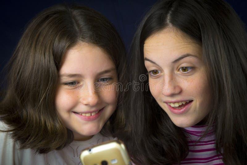 Portret dwa ślicznej siostry patrzeje telefon komórkowego zdjęcie stock