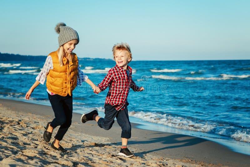 Portret dwa śmiesznego białego Kaukaskiego dziecka żartuje przyjaciół bawić się biegać na oceanu morza plaży na zmierzchu fotografia royalty free