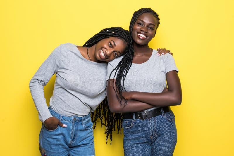 Portret dwa afrykańskiej młodej kobiety ściska i śmia się nad żółtym tłem obraz royalty free