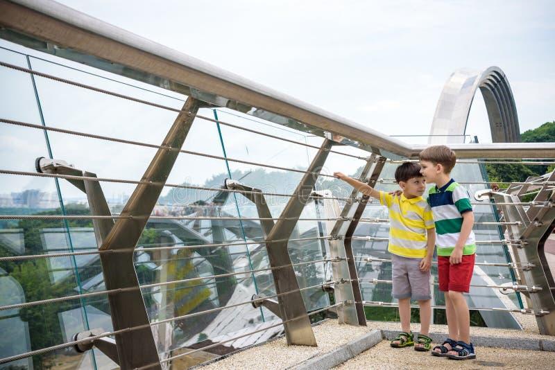 Portret dwa chłopiec żartuje spacer nad mostem i patrzeć w dół, dziecka chodzić outside w słonecznym dniu, Młode chłopiec relaksu obrazy stock