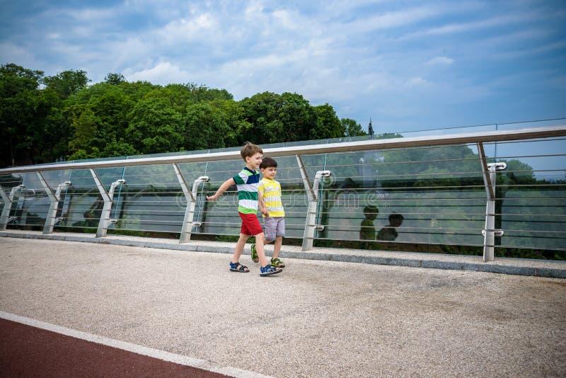 Portret dwa chłopiec żartuje spacer nad mostem i patrzeć w dół, dziecka chodzić outside w słonecznym dniu, Młode chłopiec relaksu zdjęcie royalty free