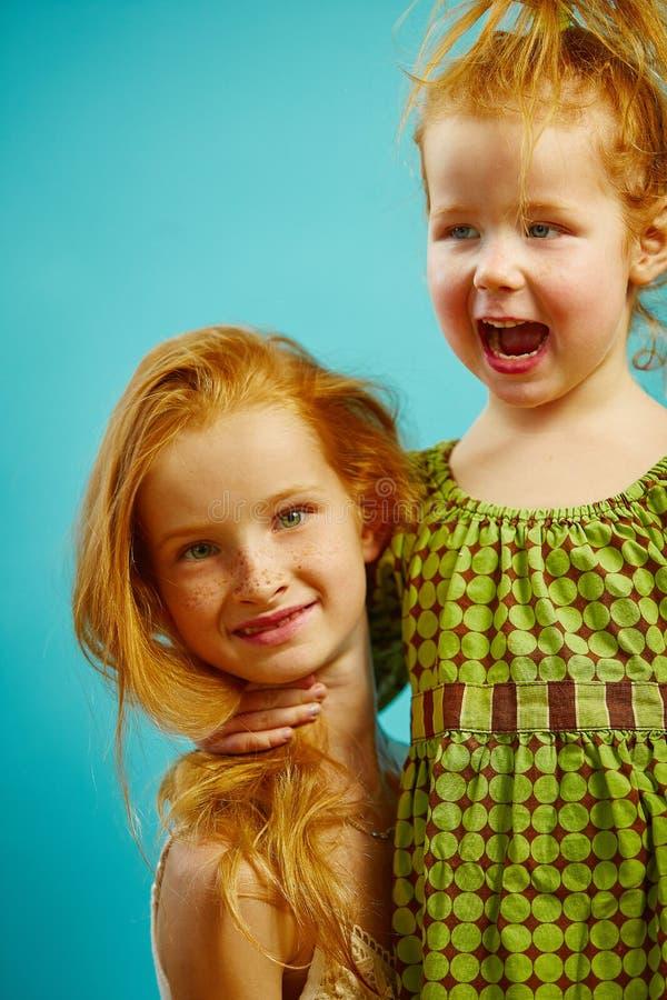 Portret dwa czerwień przewodził małe siostry ściska, wyrażający ciepłego związek obraz royalty free