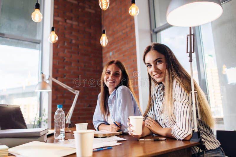 Portret dwa dosyć one uśmiechają się młodej kobiety patrzeje kamery obsiadanie przy pracy biurkiem Żeńscy freelancers pracuje w d fotografia royalty free