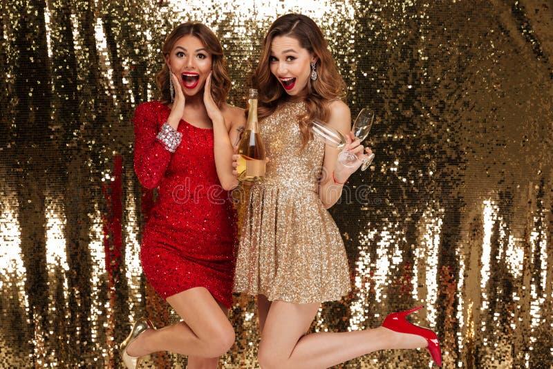 Portret dwa excited atrakcyjne dziewczyny w błyszczących sukniach obrazy royalty free