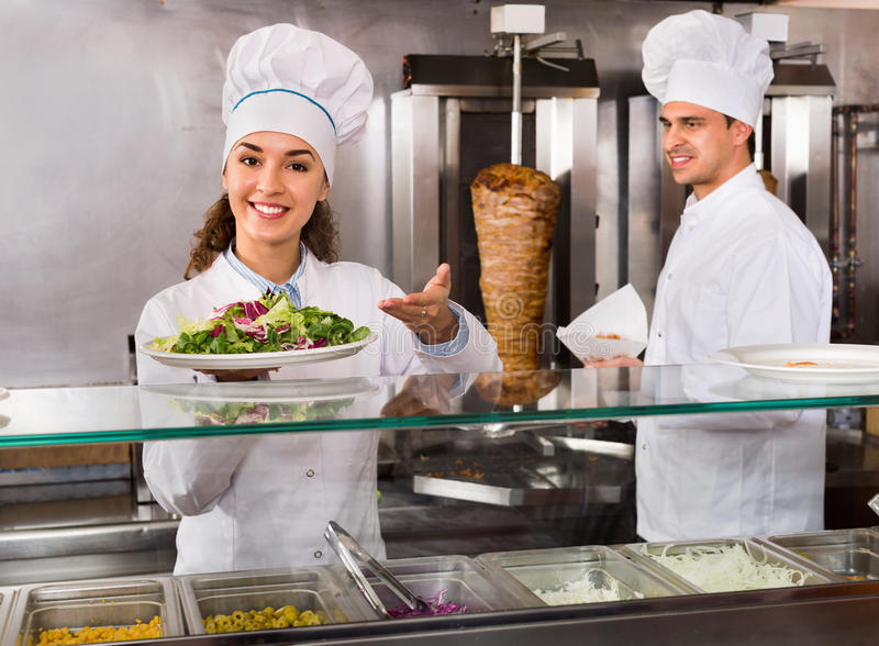 Portret dwa gościnnego szefa kuchni z kebabem przy fastfood miejscem fotografia royalty free