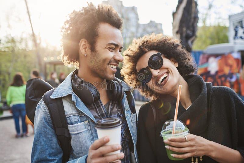 Portret dwa kochanka z afro ostrzyżeniami, spaceruje w parkowej i pije kawie podczas gdy opowiadający wydawać i cieszący się zdjęcia stock