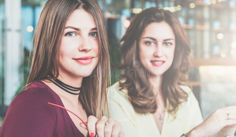 Portret dwa młodej przystojnej uśmiechniętej dziewczyny z długie włosy Bizneswoman w przedpolu trzyma szkła w jej ręce obraz royalty free