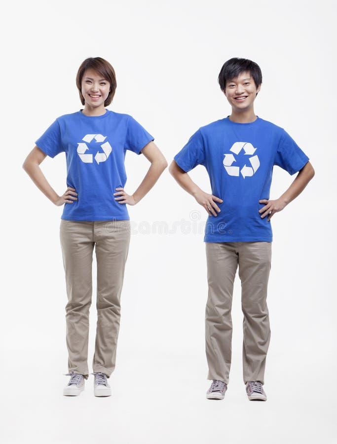 Portret dwa młodzi ludzie jest ubranym przetwarzający symbol koszulki, studio strzał obraz royalty free