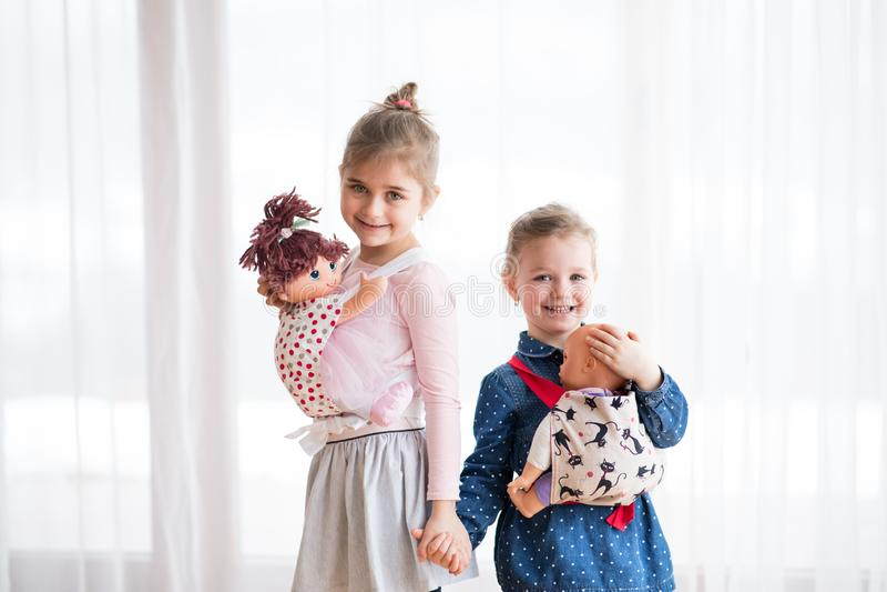 Portret dwa małej dziewczyny stoi lale w dziecko przewoźnikach indoors i niesie zdjęcie royalty free