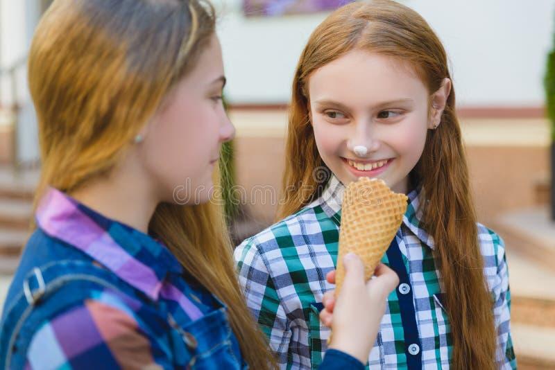 Portret dwa nastolatek dziewczyny stoi wpólnie jeść lody obraz stock