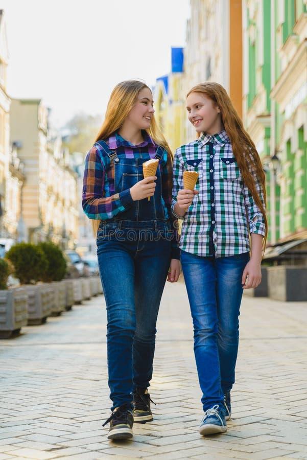 Portret dwa nastolatek dziewczyny stoi wpólnie jeść lody obrazy royalty free