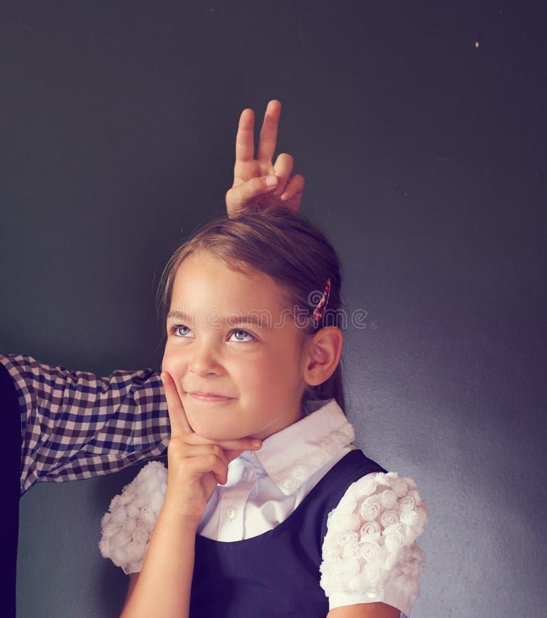 Portret dwa pięknego europejczyka dzieciaka chłopiec i dziewczyna w mundurek szkolny pozyci obok blackboard Chłopiec pokazuje rog fotografia royalty free