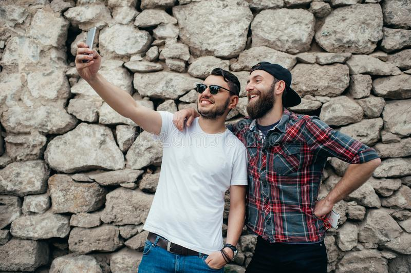 Portret dwa z podnieceniem młodego człowieka bierze selfie podczas gdy stojący wpólnie nad kamiennej ściany tłem zdjęcia stock