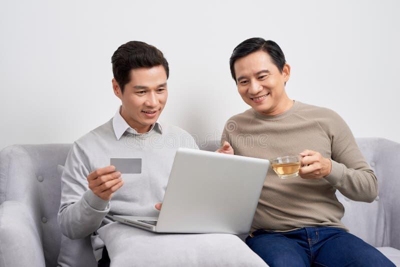 Portret dwa z podnieceniem młodego człowieka trzyma laptop podczas gdy wskazujący palec przy kartą kredytową i świętujący w żywym obraz royalty free