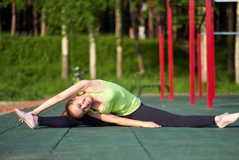 Portret dysponowana i sporty młoda kobieta robi rozciąganiu w treningów sportach gruntuje zdjęcia royalty free