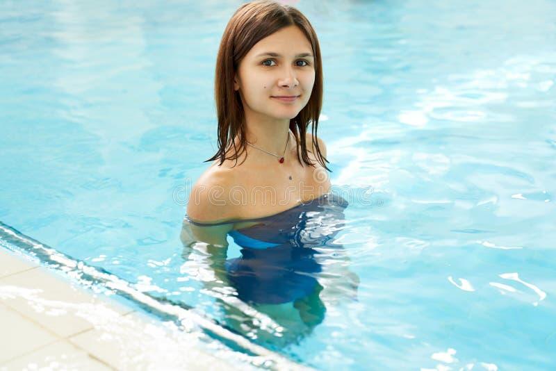 Portret dysponowana młoda kobieta w basenie Szcz??liwa u?miechni?ta p?ywaczki kobieta w basenie podczas gdy trenuj?cy fotografia stock