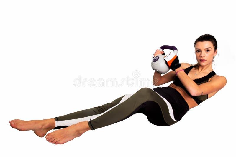 Portret dysponowana zdrowie kobieta robi intensywnemu sedno treningowi z kettlebell niezrównoważenie obrazy stock
