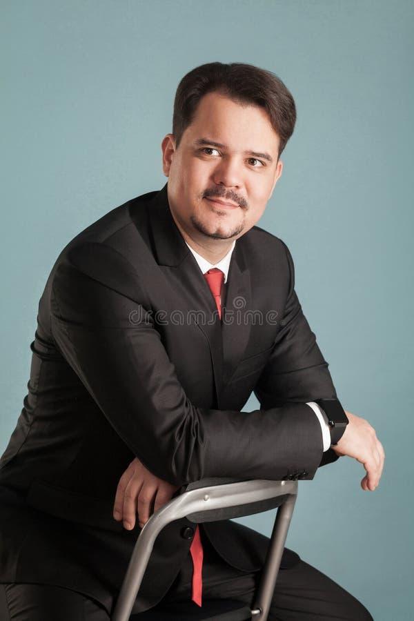 Portret działanie krótkopędu siedzący biznesmen, mały uśmiech na fa obrazy royalty free