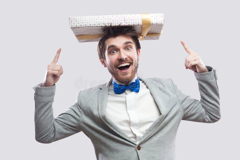 Portret dziecięcy śmieszny młody człowiek w szarość pokrywa i błękitna łęku krawata pozycja i wskazywać dotykamy przedstawiać na  zdjęcia royalty free