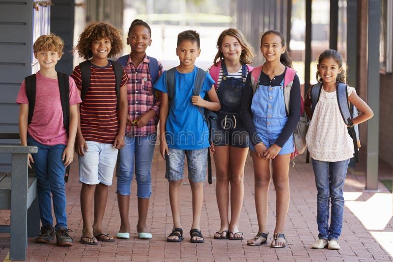 Portret dzieciaki stoi w szkoła podstawowa korytarzu fotografia stock