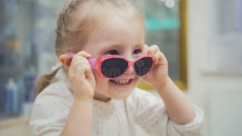 Portret dziecko w szkłach - blondynki dziewczyny próby fasonują medycznych szkła robi zakupy w okulistyki klinice fotografia stock