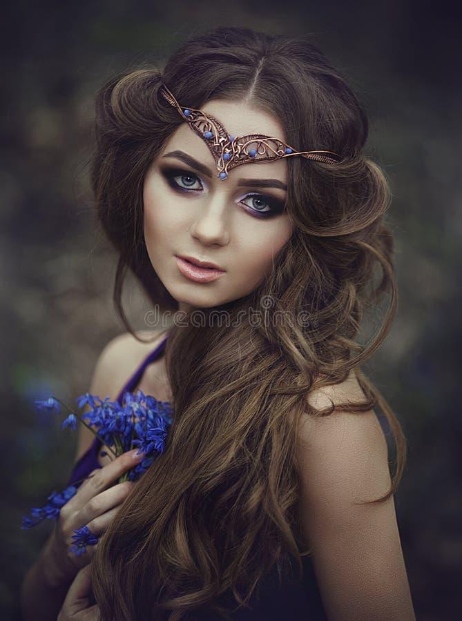 Portret dziewczyna elf z długie włosy i niebieskimi oczami, jest ubranym tiarę z bukietem wiosna kwiaty w lasowej dziewczynie fotografia stock