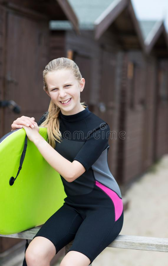 Portret dziewczyna Trzyma Bodyboard Plażowymi budami W Wetsuit fotografia stock