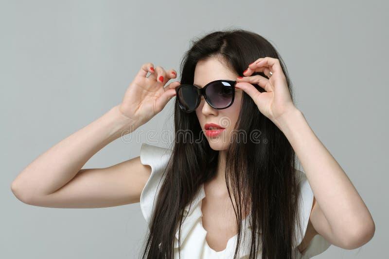 Portret dziewczyna w białej sukni która stawia dalej okulary przeciwsłonecznych zdjęcia royalty free