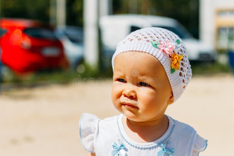 Portret dziewczyna w białej sukni troszkę białym kapeluszu z kwiatami na tle samochody i, na boisku, a obrazy stock