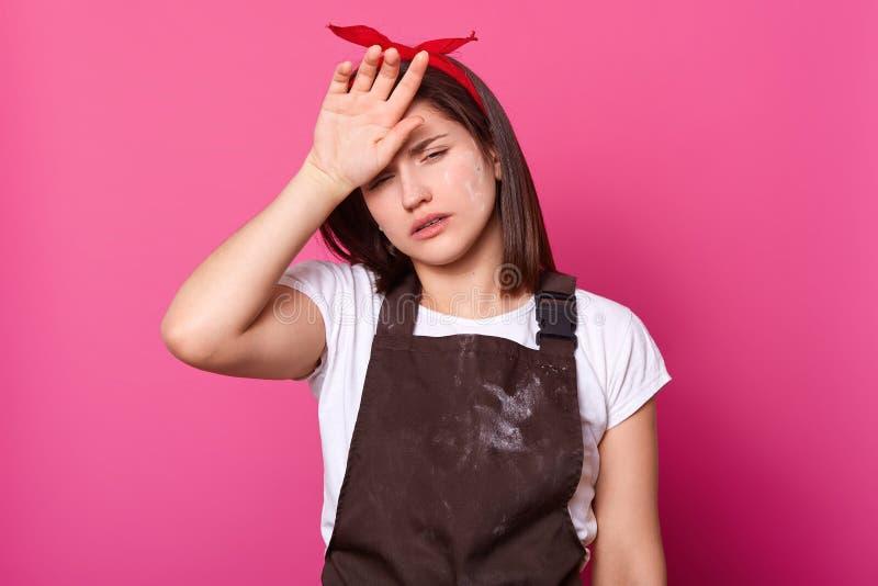 Portret dziewczyna w brązu fartuchu, biała t koszula, czerwony włosiany zespół z zmęczonym wyrażeniem na różanym tle, Model pozy  obrazy royalty free