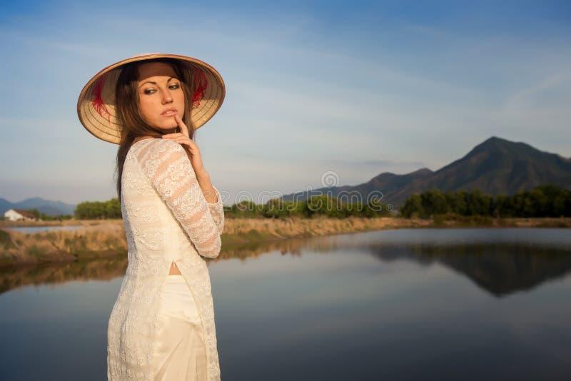 portret dziewczyna w Wietnamskim kapeluszu przeciw krajów jeziorom obrazy royalty free