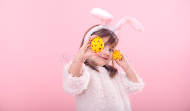 Portret dziewczyna z królików ucho w Wielkanocnymi jajkami troszkę zdjęcia stock