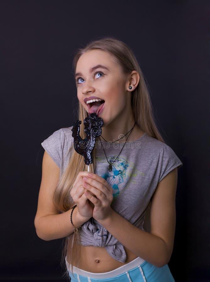 Portret dziewczyna z lizakiem na czarnym tle zdjęcie stock