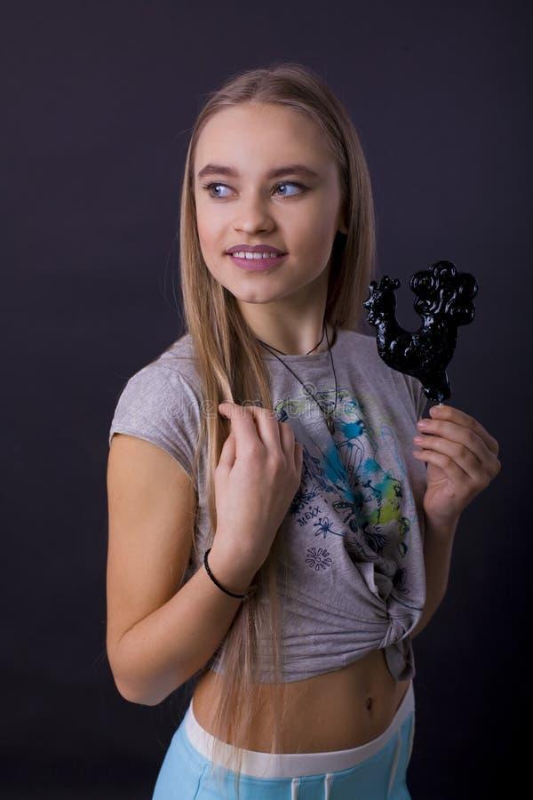 Portret dziewczyna z lizakiem na czarnym tle zdjęcia stock