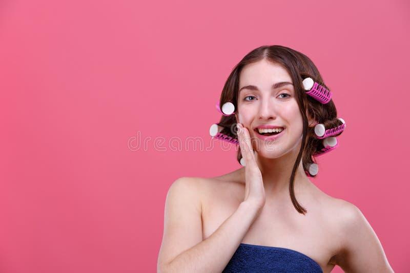 Portret dziewczyna z włosianymi curlers na włosy, uśmiechnięta mienie ręka blisko twarzy Na różowym tle obrazy stock