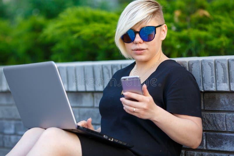 Portret dziewczyny uczeń outdoors opowiada na telefonie obraz royalty free