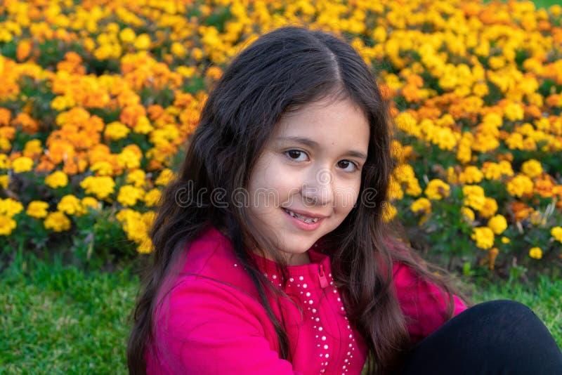 """Portret dziewczyny z 9-letnim zaczepem na zÄ™bach siedzi na tle żółtych kwiatów i uÅ›miecha siÄ™ w sÅ'oneczny dzieÅ"""" zdjęcia royalty free"""