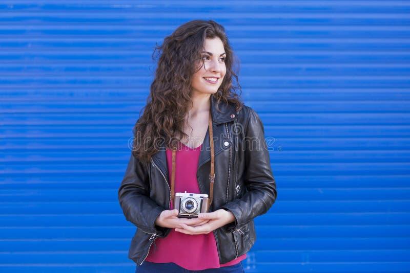 Portret een jonge mooie vrouw die een uitstekende camera over B houden stock fotografie