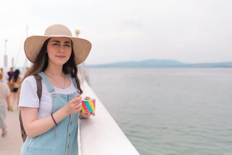 Portret Een jonge mooie vrouw in een hoed die, die op de balustrade leunen en voor de camera stellen De ruimte van het exemplaar stock fotografie