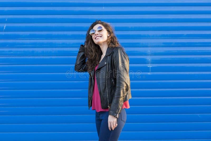 Portret een jonge mooie vrouw met moderne zonnebril over blu stock fotografie