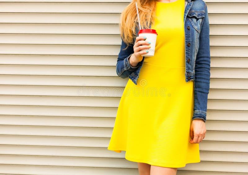 Portret Een meisje in een mooi geel de zomerkleding en een jeansjasje rust met een koffie op een de zomerdag Een deel van het lic stock foto