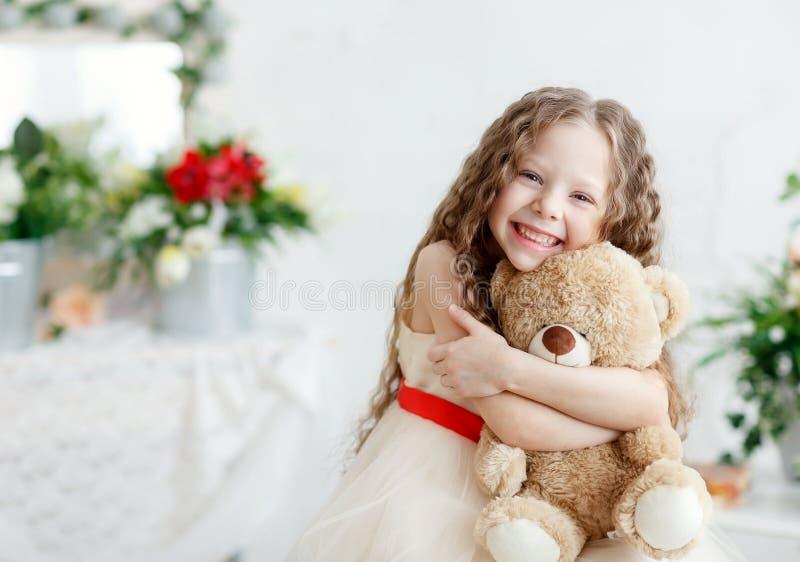 Portret ekspresyjna mała piękno dziewczyna ściska ogromnego mokietu niedźwiedzia, salowy strzał na białym pokoju dziewczyny d?ugi obraz royalty free