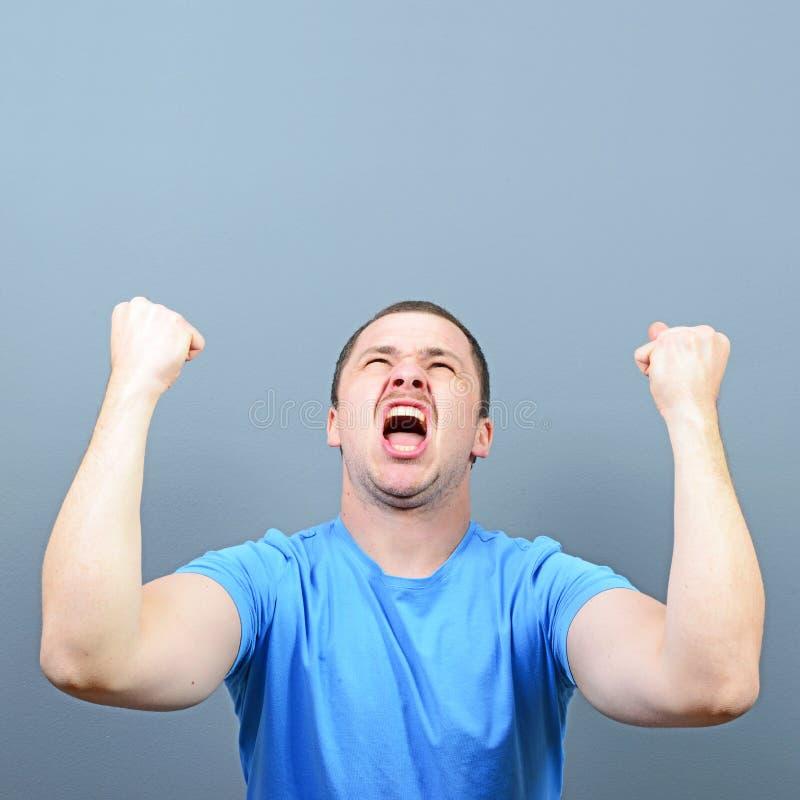 Portret ekstatyczny młody człowiek odświętności zwycięstwo lub wygrana przeciw szaremu tłu obraz stock