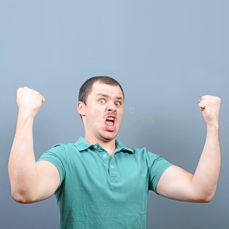 Portret ekstatyczny młody człowiek odświętności zwycięstwo lub wygrana przeciw szaremu tłu zdjęcie stock