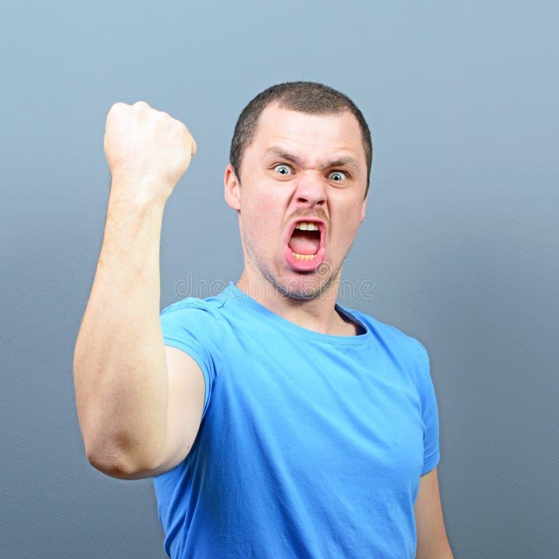 Portret ekstatyczny młody człowiek odświętności zwycięstwo lub wygrana przeciw szaremu tłu zdjęcia stock