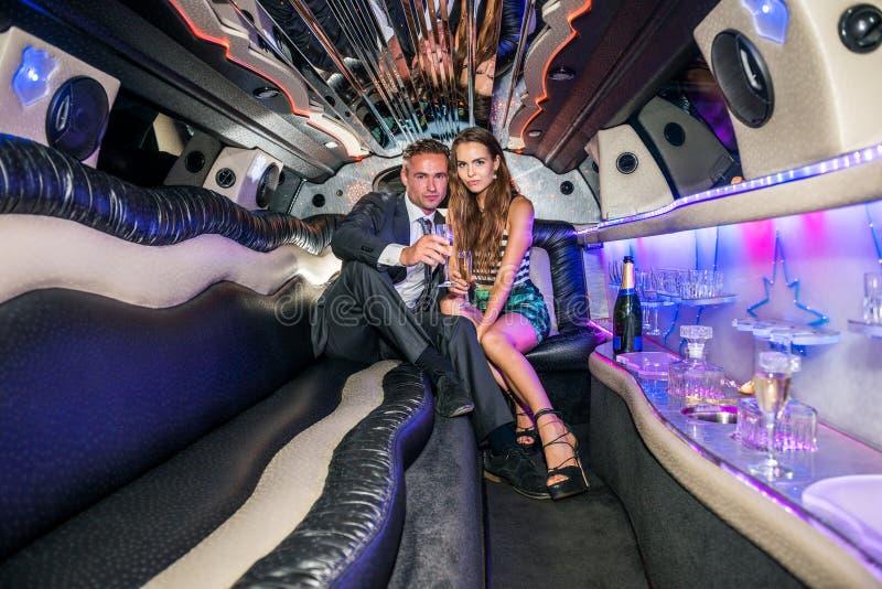Portret eleganccy potomstwa dobiera się z szampańskimi fletami w limous zdjęcie royalty free