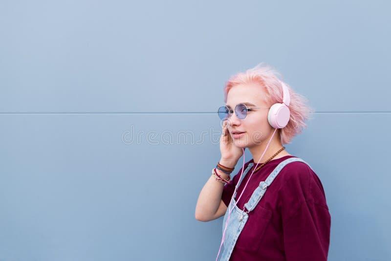 Portret elegancka dziewczyna w szkłach, blondynie i hełmofonach, słucha muzyka na tle błękitna ściana fotografia royalty free
