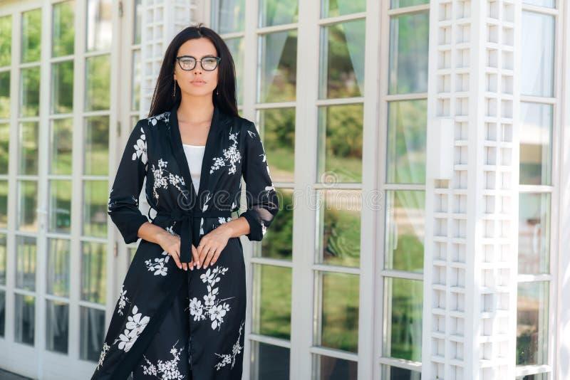 Portret elegancka piękna Europejska kobieta jest ubranym eyeglasses w modnym położeniu Biznesowa dama jest ubranym a zdjęcia royalty free