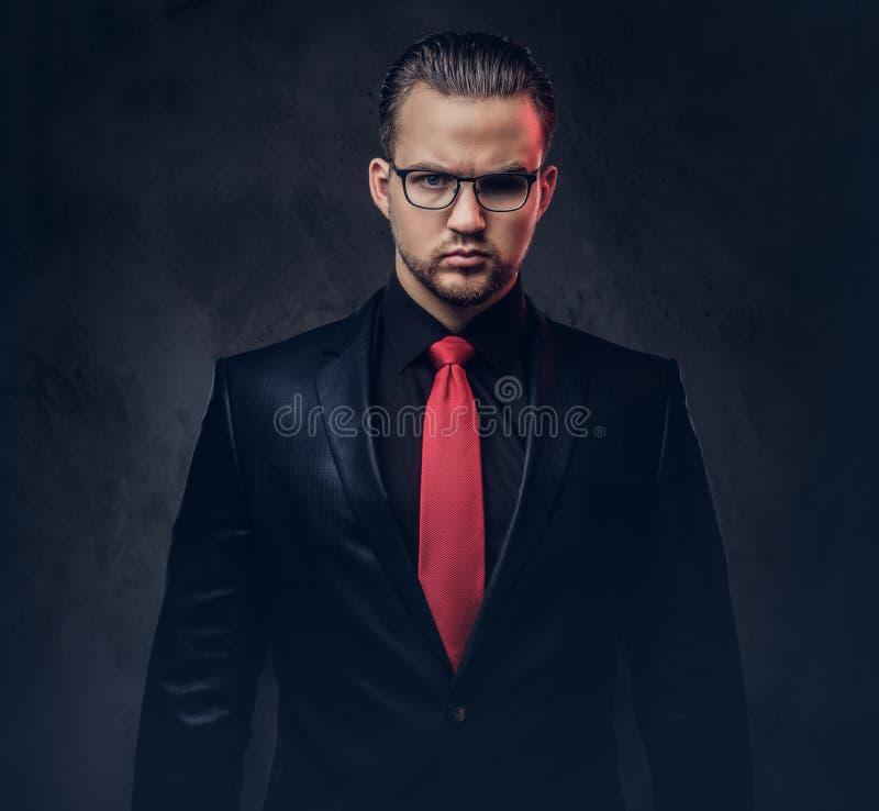 Portret elegancka samiec w czarnym kostiumu czerwonym krawacie i Odizolowywający na ciemnym tle zdjęcia stock